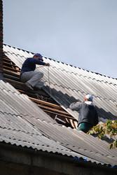 Чоловіки латають дах