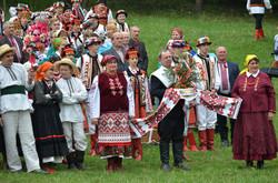 Учасники фестивалю тримають прикрашений коровай