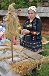 Жінка плете пряжу на веретені